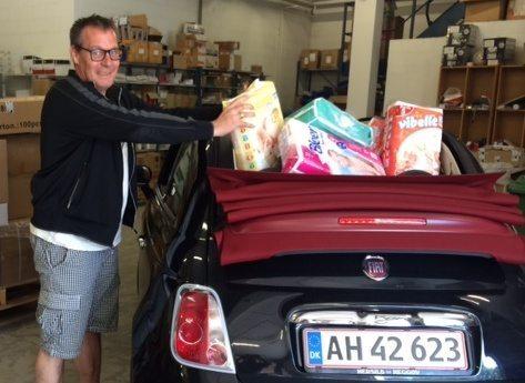 Steen Mogensen fra Thomas Cook Airlines tømmer sin bil for bl.a. bleer og gør 18 store kasser klar til flygtningefamilierne på Lesbos.