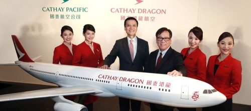 Cathay Pacifics koncernchef, Ivan Chu, nr. 3 fra venstre, og Dragonairs ditto, Algernon Yau, med flymodel med Cathay Dragons nye bemaling. I baggrunden ses de to selskabers logo – Cathays grønne vinge og Dragons røde.