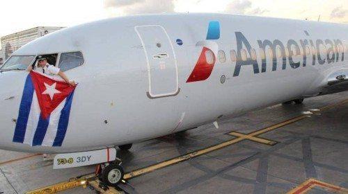 Kevin Mase, chefpilot hos American Airlines, vifter med et cubansk flag fra et American-fly i midten af december, dagen efter USA og Cuba blev enige om atter at tillade passagerflyvninger mellem de to lande.