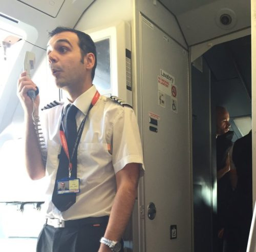 Flyets kaptajn fortæller passagererne, hvad der er sket og beklager forsinkelsen. Foto fra Twitter.