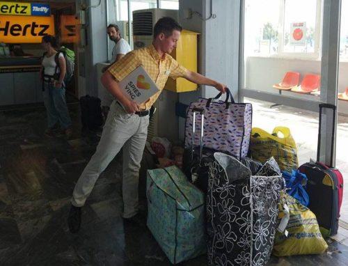 En af Spies guider, Sebastian Diggins, samler gæsternes hjælpepakker i lufthavnen på Lesbos, inden de hentes af frivillige fra den lokale kirke.